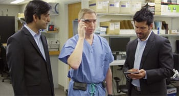 Doctor activating Google Glass while talking with 2 developers.