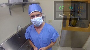 Doctor in OR with vital signs in top right corner of view.